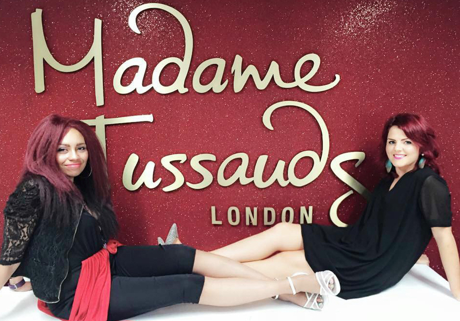 Soulshine Band, funk soul wedding band 2 female singers sat on the floor infront of red wall displaying large Madame Tussauds logo in gold writing